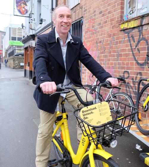 Cllr Douglas Johnson riding an Ofo bike