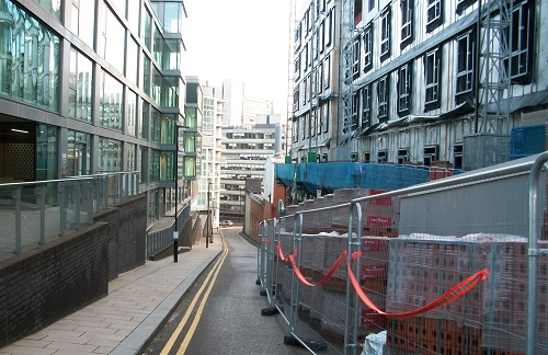 Builders' scaffolding and fencing filling the road opposite residential flats